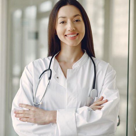 Woman in a uniform. Doctio with a stethoscope. Brunette in a hall.